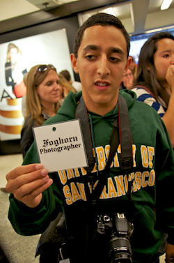 A student photojournalist from the University of San Francisco holding up a credential at a protest he was covering in 2011.
