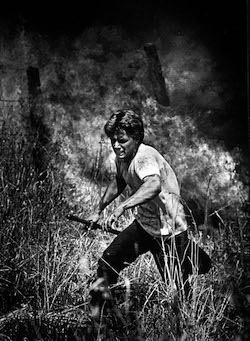 An inmate at an Enfield, Conn., prison running to escape a grassfire that nearly burned him over in 1986. The photo was the first Kodas had published from a wildfire.
