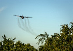 An Air Force Reserve aircrew flying a C-130 Hercules performs aerial spraying of mosquitoes