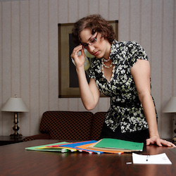 Woman looking over folders on conference table