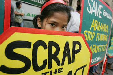 A young protester holds a placard during an anti-mining rally in the financial district of Makati, south of Manila, Philippines, April 23, 2007 (AP photo by Aaron Favila).